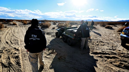 Agents from the NTSB and the FBI survey the debris from SpaceShipTwo in a desert field near the crash site on November 1, 2014, in Mojave, California.