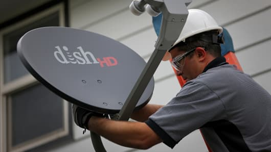 A field service specialist for Dish Network installs a satellite television system at a residence.