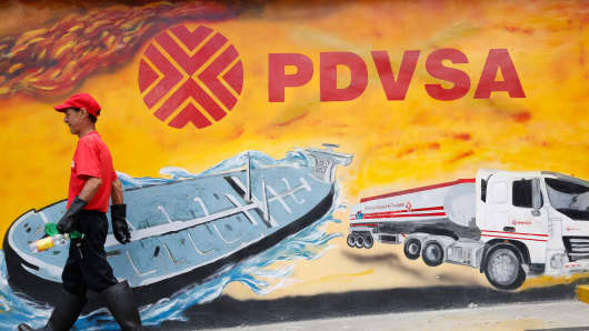 A worker walks past a mural with a PDVSA logo at its gas station in Caracas, Venezuela.