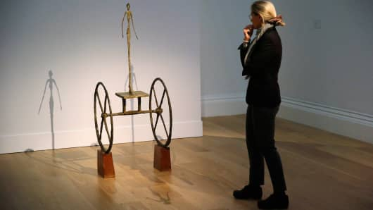 A visitor looks at Chariot by Alberto Giacometti at Sotheby's auction house in London.