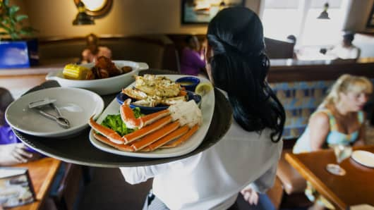 A waitress carries a tray a lobster kettle and a crab trio dish at a Red Lobster restaurant in Yonkers, N.Y.