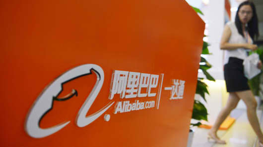 A woman walking past Alibaba signage in Hangzhou, China.