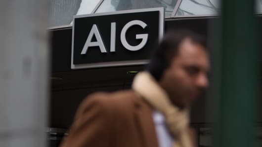 A pedestrian walks past the American International Group offices in New York.