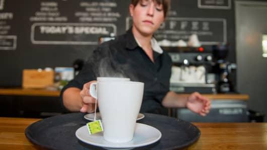 A waitress prepares tea for customers at Mina's Mediterraneo, in Miami Shores, Florida.