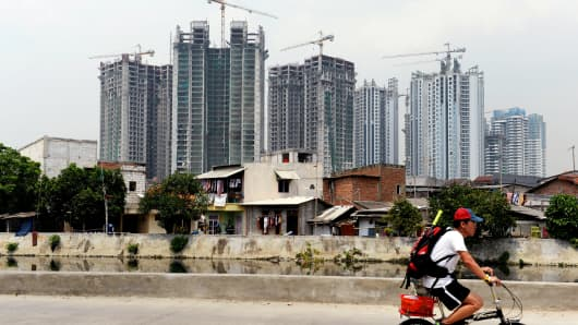 A man rides a bicycle past residential apartment buildings under construction in Jakarta, Indonesia.