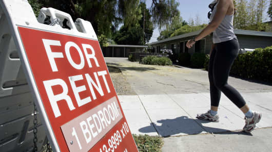 "A woman walks next to a ""For Rent"" sign at an apartment complex in Palo Alto, California."