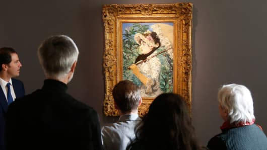 """Visitors look at the painting """"Le Printemps"""", 1881, by French painter Edouard Manet during its presentation at Christie's Auction House in Paris October 22, 2014."""