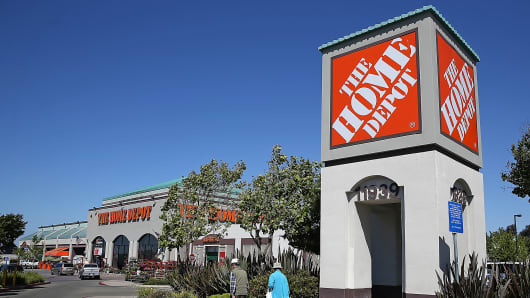 People walk by a sign in front of a Home Depot store in El Cerrito, Calif.