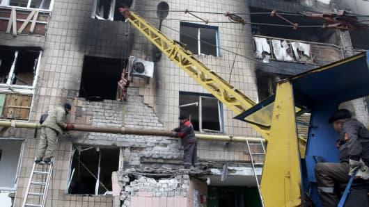 Officials rebuild the damaged building after shelling in rebel-held Donetsk, east of Ukraine on November 7, 2014.