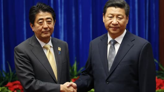 China's President Xi Jinping shakes hands with Japan's Prime Minister Shinzo Abe in Nov 10, 2014 during their meeting at the Great Hall of the People, on the sidelines of the Asia Pacific Economic Cooperation.