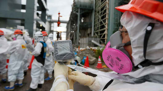 File photo: A worker wearing protective clothing and mask measures the radiation in the air as employees prepare materials used to create a frozen underground wall to surround the crippled reactor buildings at Tokyo Electric Power Co.'s (Tepco) Fukushima Dai-ichi nuclear power plant in Okuma, Fukushima Prefecture, Japan, on Wednesday, July 9, 2014.