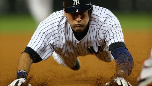 Derek Jeter #2 of the New York Yankees slides into third base.