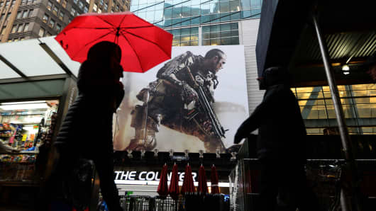 People walk past a billboard advertising the latest installment of 'Call of Duty' video game near Times Square in New York on November 6, 2014.