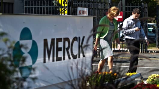Employees walk past a Merck sign in front of the company's building in Summit, N.J.