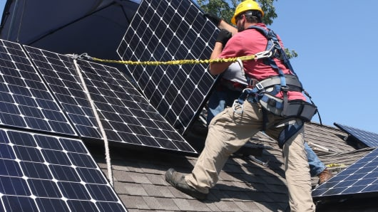 Workers install Solar Service Inc. photovoltaic (PV) solar electric panels on the roof of a home in Park Ridge, Illinois.