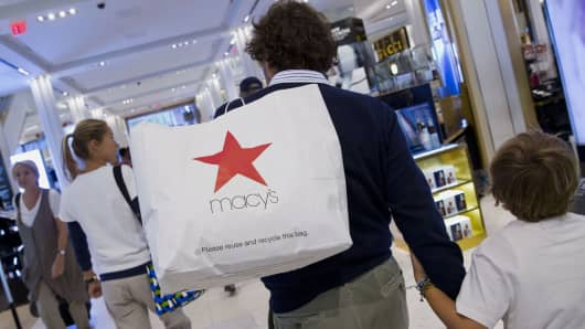 A customer carries a shopping bag while walking through the Macy's Inc. flagship store in New York.
