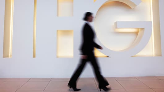 An employee passes a logo in the reception area of InterContinental Hotels Group's headquarters in Denham, U.K.