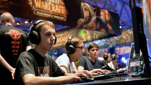 Visitors try the massively multiplayer online role-playing game 'World Of Warcraft' at the Blizzard Entertainment stand at the 2014 Gamescom gaming trade fair on August 14, 2014 in Cologne, Germany.