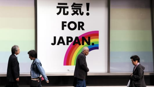 Pedestrians walk past an advertisement for a post-quake reconstruction project in Tokyo, Japan.
