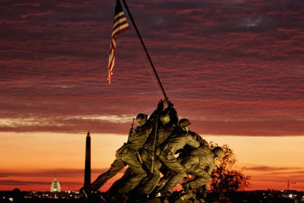 The early morning sun begins to rise behind the Iwo Jima Memorial in Arlington, Virginia.