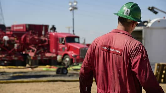 A Halliburton worker walks through an Anadarko Petroleum Corporation hydraulic fracturing site north of Dacono, Colo., Aug. 12, 2014.
