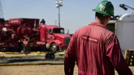 A Halliburton worker walks through an Anadarko Petroleum Corp. hydraulic fracking site north of Dacono, Colorado.