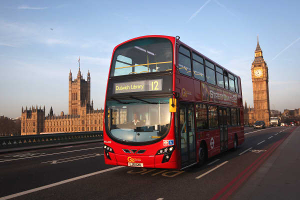 A double decker bus makes its way over Westminster Bridge, past the Houses of Parliament and Big Ben in London, England.