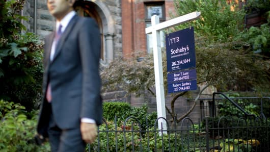 A Sotheby's International Realty sign stands outside of a townhouse for sale in Washington, D.C.