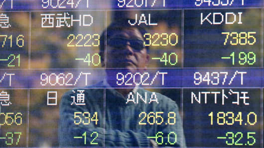 A man is reflected on an electronic stock quotation board outside a brokerage in Tokyo, November 17, 2014.