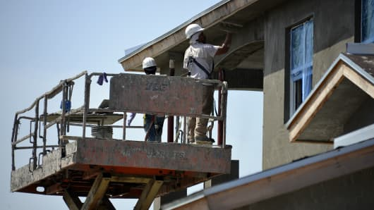 Workers apply stucco to a building under construction at the Toll Brothers Jupiter Country Club housing development in Jupiter, Florida.