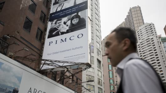A man walks past a Pacific Investment Management Company LLC (PIMCO) advertisment which is displayed on a building in Hong Kong, China.
