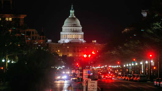 The U.S. Capitol stands at night in the background as a red light is displayed on a traffic signal in Washington, D.C.