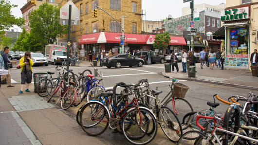 A row of bicycles are parked at the 7th Ave subway station in Williamsburg, Brooklyn.