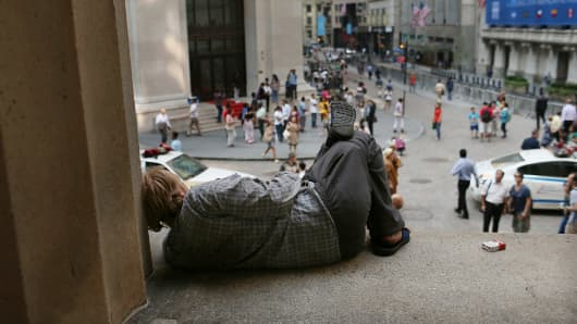 A homeless man rests along Wall Street in front of the New York Stock Exchange in New York Citу.