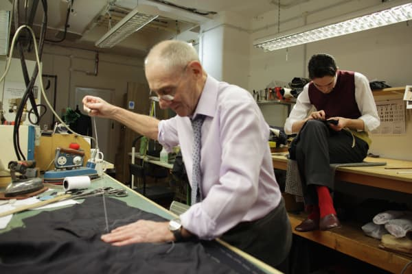 Tailors work on a garments in the work room in London.