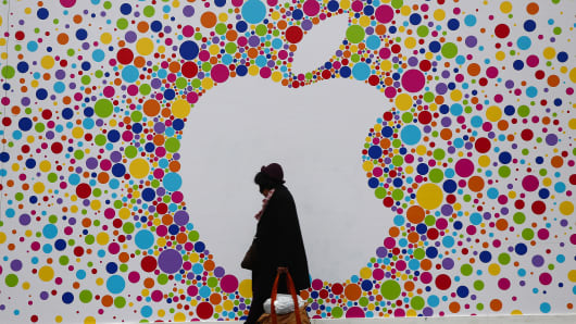 A pedestrian carries a shopping bag as she passes a giant Apple logo outside a new Apple store, still under development.