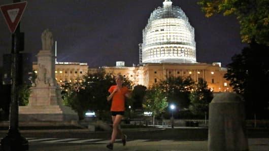 A woman jogs near U.S. Capitol building in Washington.