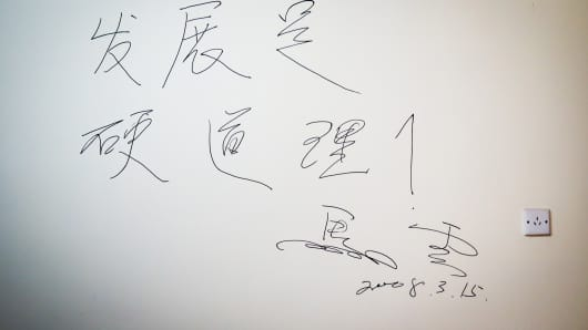 "Writing on the wall of Jack Ma's old apartment that translates roughly as ""The core of the company is to grow and grow""."