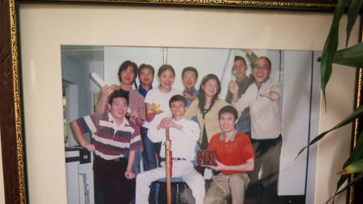 A photo of Jack Ma and employees of Alibaba Group back in 2003 hangs in his old apartment in Hangzhou, China.