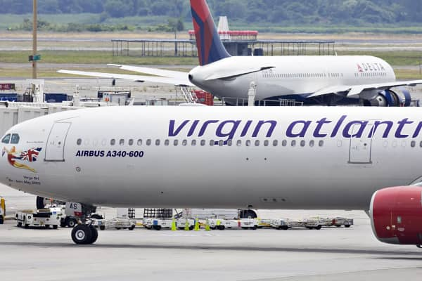 A Virgin Atlantic plane taxis past a Delta plane at John F. Kennedy International Airport in N.Y.
