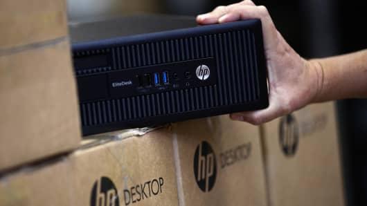 An employee selects a HP EliteDesk desktop computer in a warehouse.