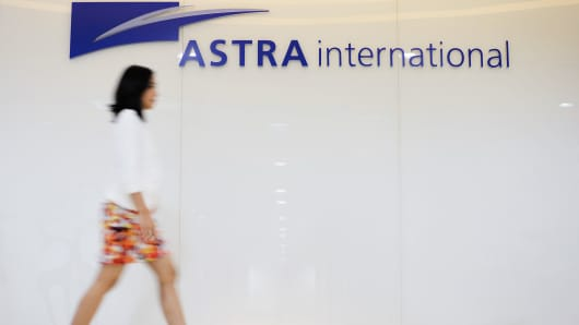 A woman walks past signage for Astra International, in Jakarta, Indonesia.