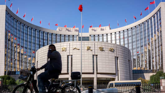 A man rides his electric bicycle passing the People's Bank of China (PBoC).