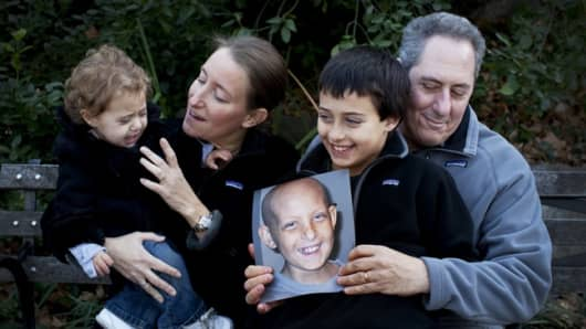 The Froman family, including Nancy Goodman, Mike Froman, and kids Ben and Sarah. They hold a photo of Jacob, who died of medulloblastoma, a rare form of brain cancer, at age 10.
