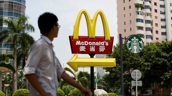 A pedestrian walks past McDonald's and Starbucks signage in the Futian district of Shenzhen, China.