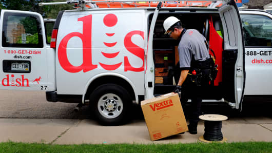 A field service specialist for Dish Network prepares to install a satellite television system at a residence in Denver.
