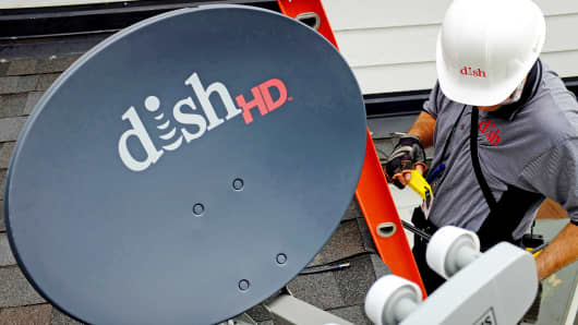 A Dish Network field service specialist installs a satellite television system at a residence in Denver.