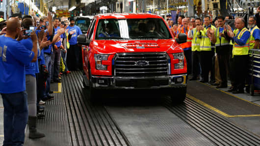 Employees cheer as the first 2015 Ford F-150 truck rolls off the production line at the company's Dearborn Truck Assembly facility in Dearborn, Michigan, Nov. 11, 2014.