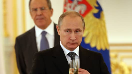 Russian President Vladimir Putin (L) holds a glass of champagne as Foreign Minister Sergei Lavrov (R) looks on during a reception for foreign ambassadors in the Grand Kremlin Palace on November 19, 2014 in Moscow, Russia.