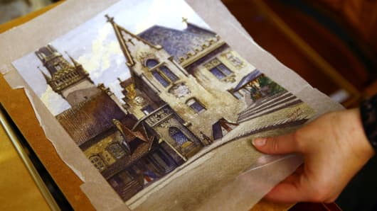 An auction house employee puts away a watercolor of the old registry office in Munich by Hitler, Nov. 18, 2014.